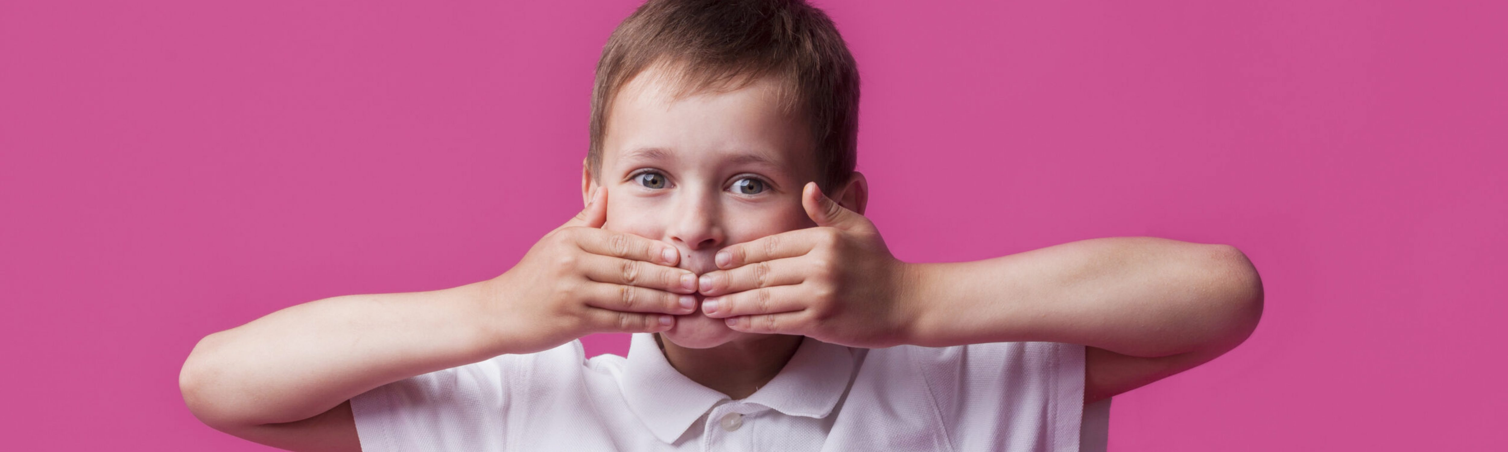portrait-of-innocent-boy-covering-his-mouth-and-looking-at-camera-over-pink-wall-background